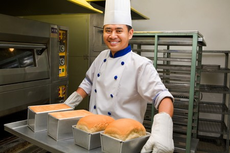 Male baker smiling while holding fresh bread from oven