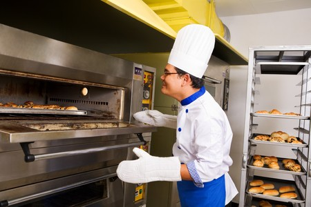 Male baker checking the bread inside oven photo