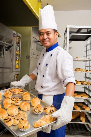 Baker holding the sweet bread fresh from the oven photo