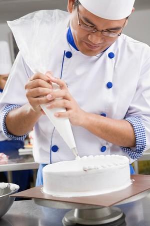 Chef-kok of Bakker verfraaien cake met witte slag room