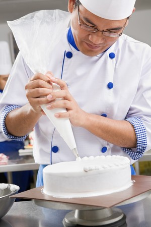 pastry: Chef or baker decorating cake with white whipped cream Stock Photo