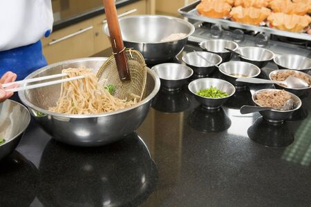 ps: Chef hand holding and stir the noodle in bowl at cooking class session. PS: movement blur on noodle being lifted by chopstick
