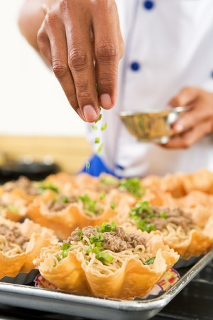 professional chef: Chef hand Sprinkle herbs on noodle. **** PS: selective focus ad noticable blur movement on the sprinkle ***** Stock Photo