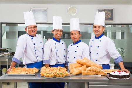 panadero: Chef o panaderos posando en la parte delantera del pan, pizza y tarta en cocina comercial