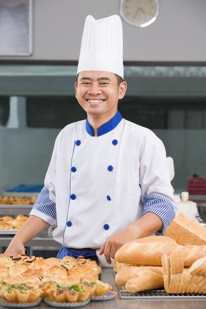 Asian chef or baker posing in front of the pastries in the commercial kitchen photo