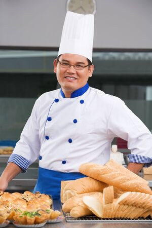 Asian chef or baker posing in front of the pastries in the commercial kitchen Stock Photo - 7283281