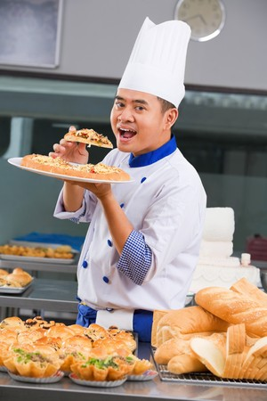 Chef eating the pizza of his won creation in front of all the pastries