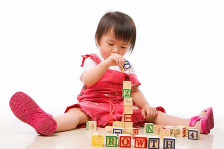 single word: Asian female toddler playing on the floor alone Stock Photo