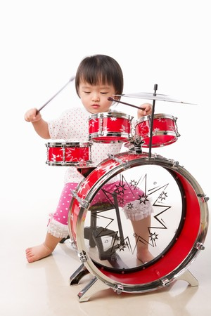 LIttle girl playing drum, shot against white background photo