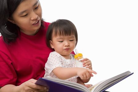 Chinese young woman story telling her cute daughter photo