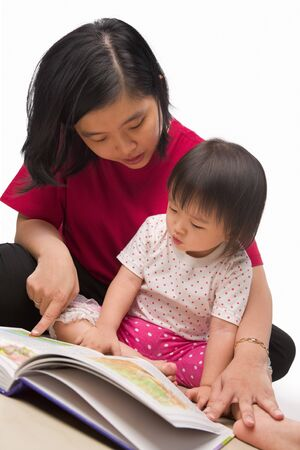 Chinese mother teaching her little girl with book photo