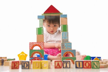 young little Asian girl looking to camera through the block windows, with EDUCATION words in front of her. photo