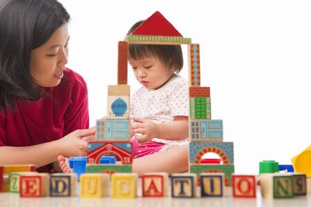 children playing together: Chinese mother and child playing together with word education in front of them