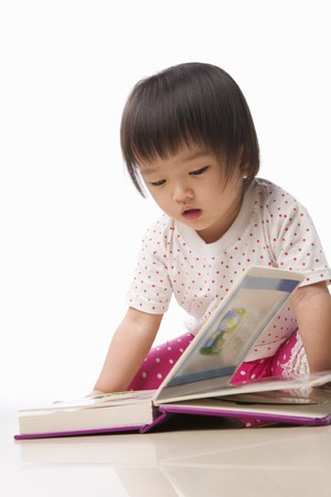 Litlle Asian girl reading book alone on floor photo