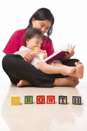 Mother and her little girl reading book with block with word Growth arranged in front of them photo