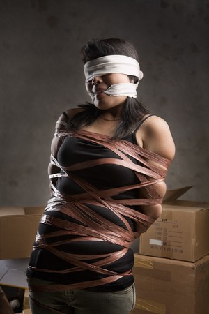 tied woman: A young woman tied-up, blind folded and muted in old room. Low key setting Stock Photo