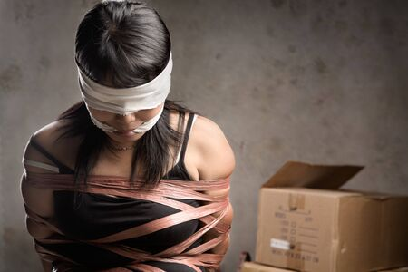 silenced: A young woman tied-up, blind folded and muted in old room. Low key setting Stock Photo
