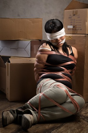 hostage: A young woman tied-up, blind folded and muted in old room. Low key setting Stock Photo