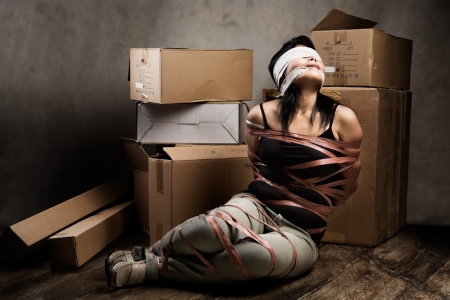 A young woman tied-up, blind folded and muted in old room. Low key setting photo