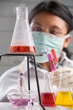 Female scientist examining boiled chemical solution in laboratory. Focus on boiled erlenmeyer Stock Photo - 7283262
