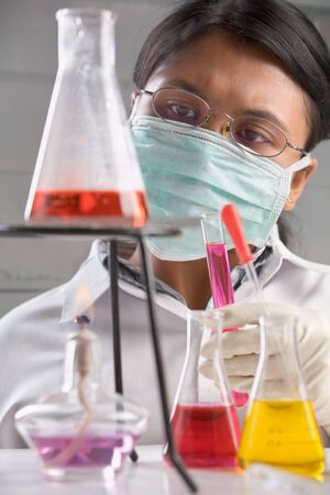 Female scientist examining boiled chemical solution in laboratory photo