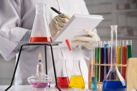 boiling tube: Scientist making notes in laboratory, focus on laboratory equipment Stock Photo