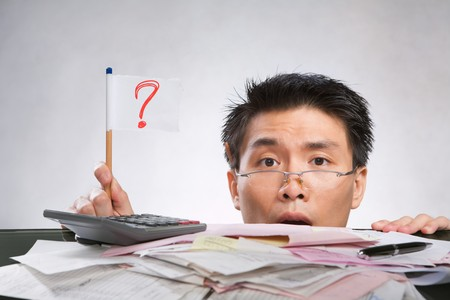 Man holding question mark flag made of paper and pencil with lots of bills in front of him Stock Photo - 7283161