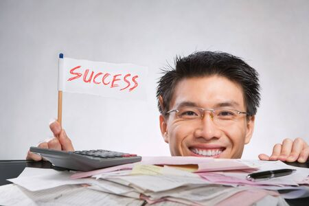 Happy man holding success flag made of paper and pencil with lots of bills in front of him Stock Photo - 7283182