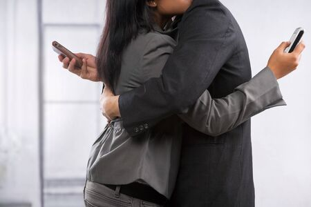 cheating: Business couple hug yet still using cell phone, can be concept for busy lifestyle of cheating Stock Photo
