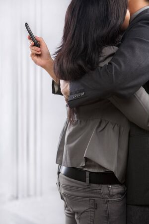 cheating woman: Business couple hug yet the man still using cell phone, can be concept for busy lifestyle of cheating Stock Photo