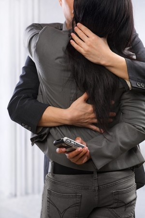 cheating: Business couple hug and kissing yet the woman still using cell phone secretly,  can be concept for busy lifestyle of cheating Stock Photo