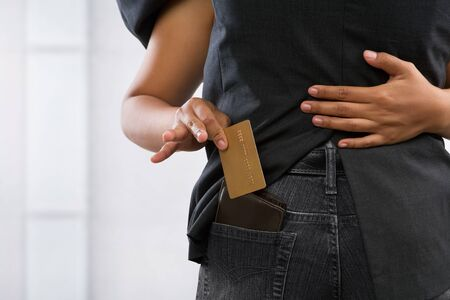 femlae hand pickpocketing gold credit card from businessman's pocket Stock Photo - 7284591