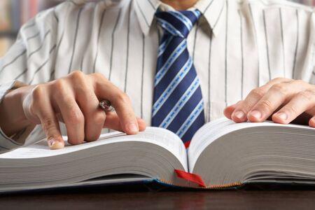 diccionarios: Diario de lectura de empresario o profesor irreconocible para buscar datos en la biblioteca  Foto de archivo