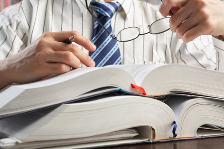 Unrecognizable businessman or professor reading journal to search for data in library Stock Photo - 7284115