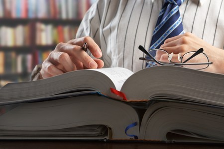 Unrecognizable businessman or professor reading journal to search for data in library Stock Photo - 7284085