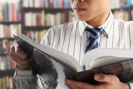 Unrecognizable businessman or professor reading journal to search for data in library Stock Photo - 7283407