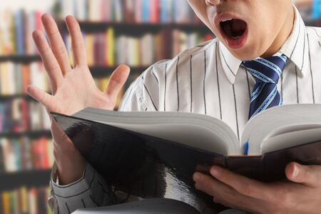 Unrecognizable businessman or professor shocked when reading a journall to search for data in library Stock Photo - 7283365