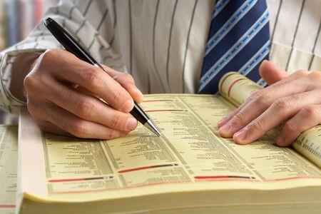 Homme d'affaires à la recherche de quelque chose dans les pages jaunes à travers les index