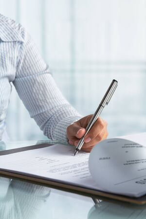 left handed: Businesswoman using left hand signing agreement paper in the office