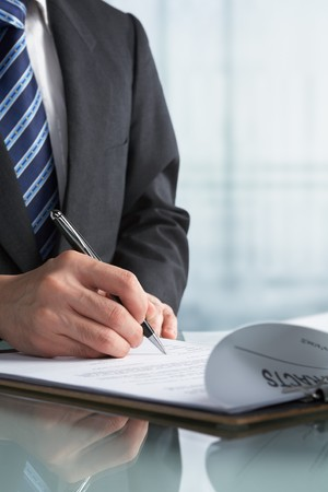 firmando: Empresario firma papel de contrato en la Oficina  Foto de archivo