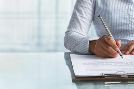 signing: Businesswoman firma accordo carta in ufficio  Archivio Fotografico