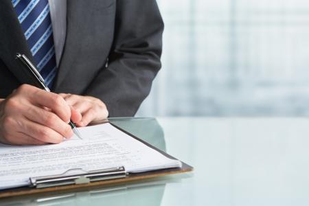 signing: Imprenditore firma contratto carta in ufficio