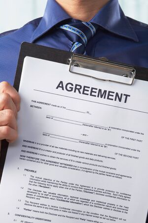 Businessman holding agreement paper, taken close up with no face Stock Photo - 7284624