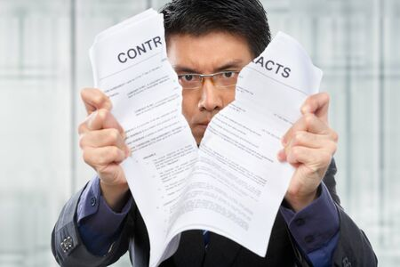 Chinese businessman tearing up the contrat papers