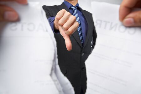 Businessman showing thumb down while the contracts tearing out photo