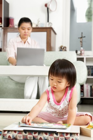 Little girl playing alone  while her mother working on background photo