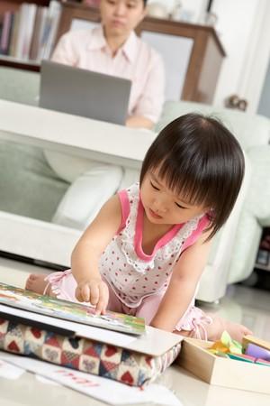 asian home: Bambina giocare da solo mentre la madre lavora sullo sfondo