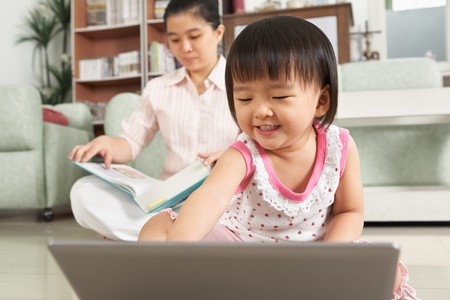 LIttle girl playing laptop with her mother or nanny on background studying photo