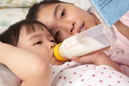 Mother telling a story to her daughter while drinking milk photo