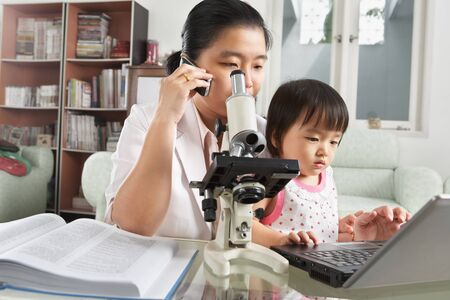Chinese busy mother try to play with her daughter while she is working photo